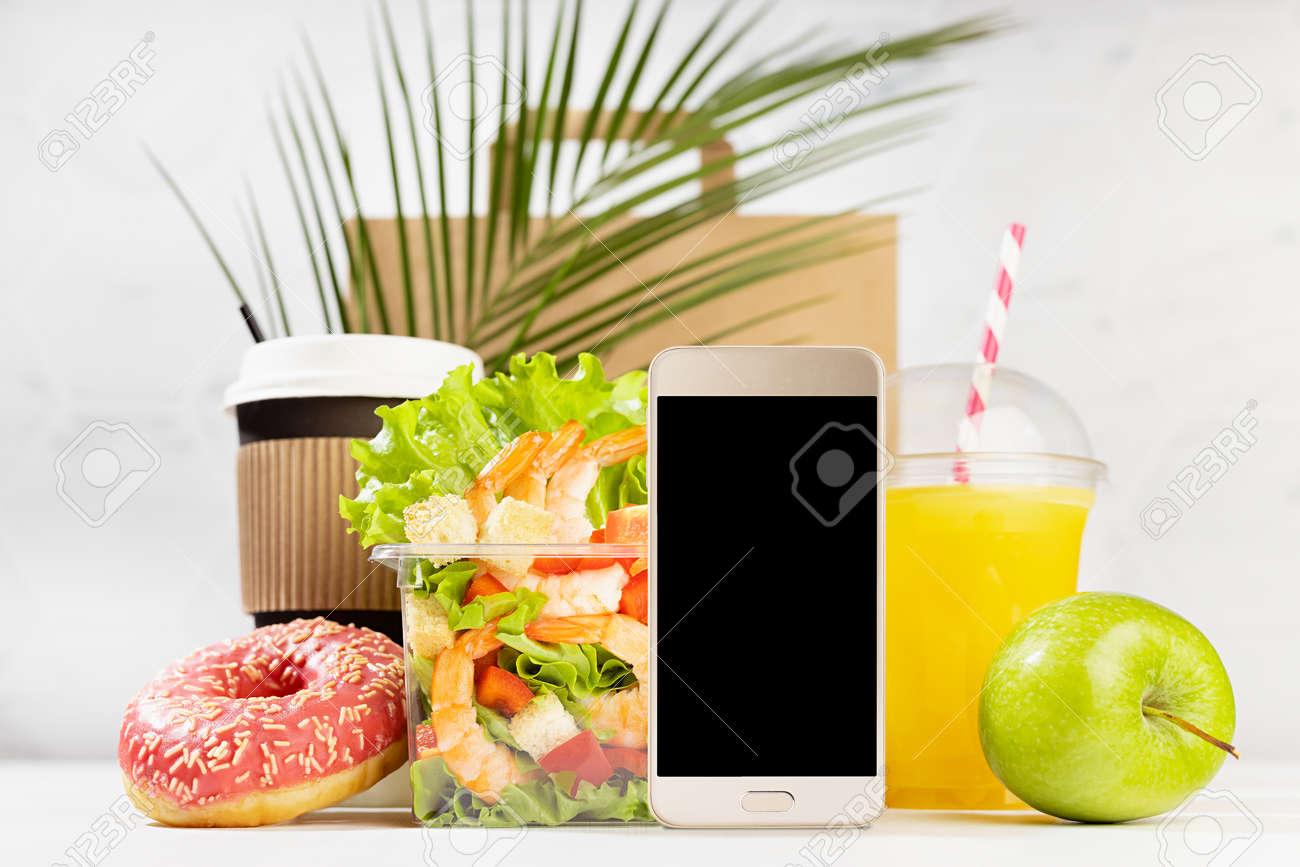 Wellness summer food set of coffee cup, orange juice, donut, tropical shrimp salad, apple in white bar interior, palm leaf. Advertising for restaurant take away, delivery food service, online order. - 173913957
