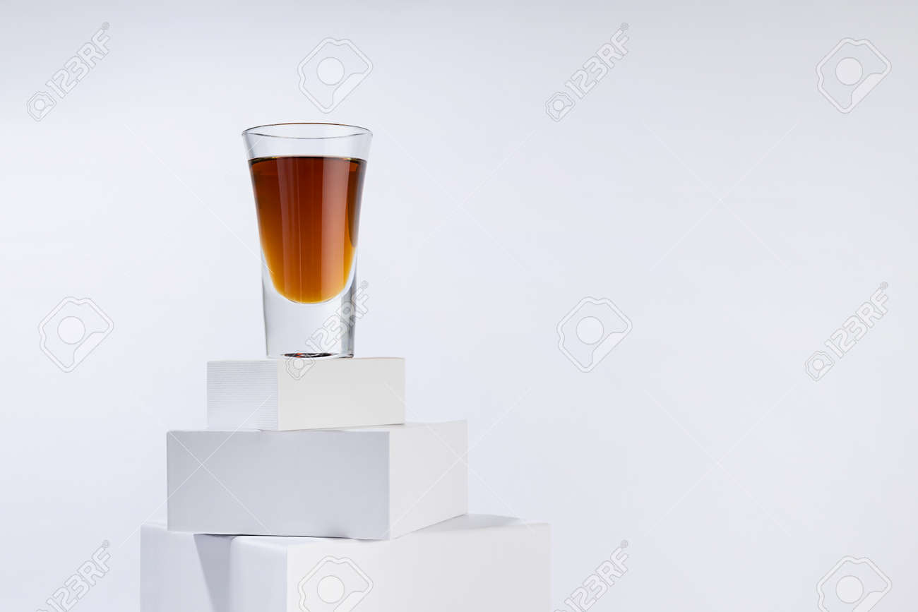 Brown old cognac in shot glass on stack of white boxes as podium in soft light white abstract space, luxury minimal geometric style. - 173913726