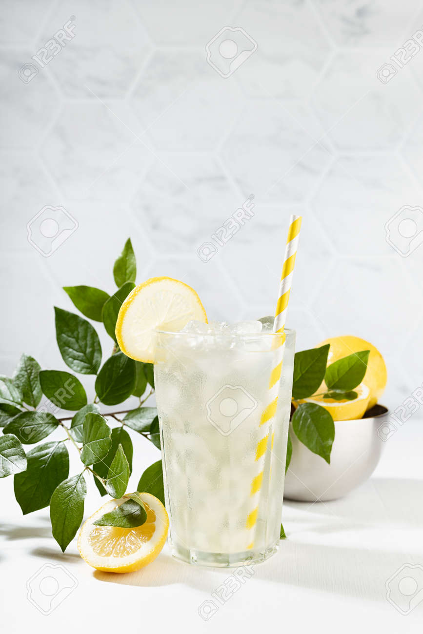 Lemon juice in soft light elegant white kitchen with green leaves in sunny day - lemonade in glass with straw, ice cubes with ingredients in silver bowl, vertical. - 173913571