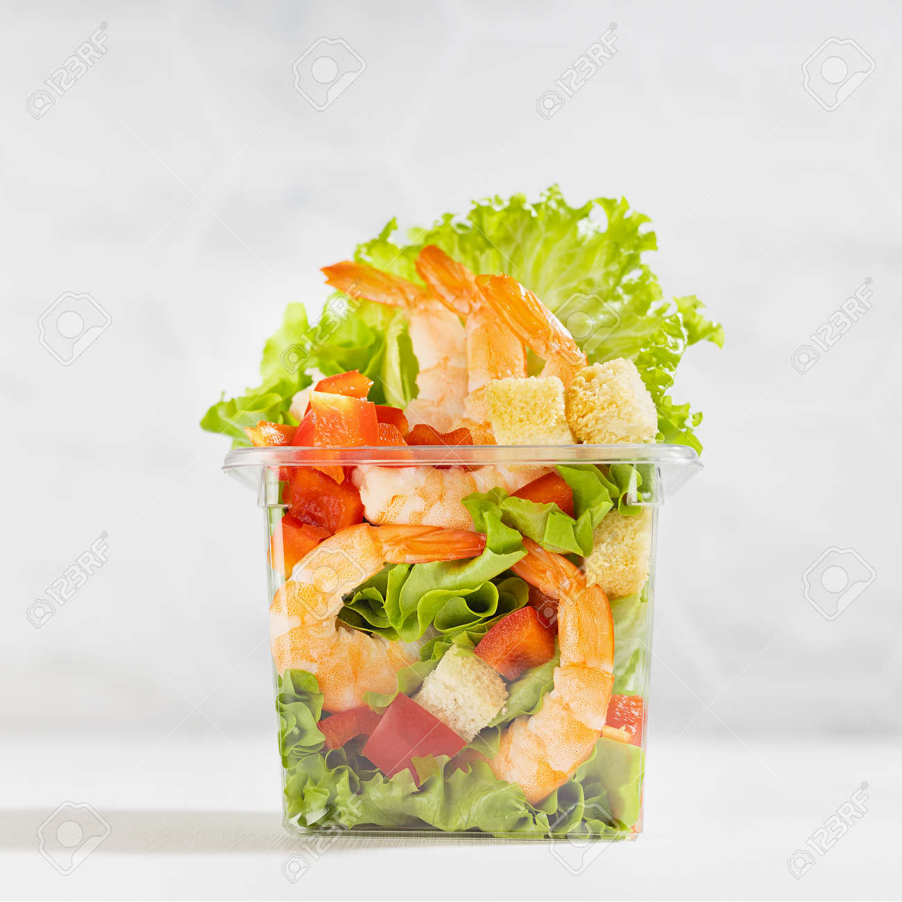 Healthy fresh summer salad with shrimps and vegetables in plastic box in soft light white kitchen interior with marble tile, closeup, square. Organic food take aw - 173913913
