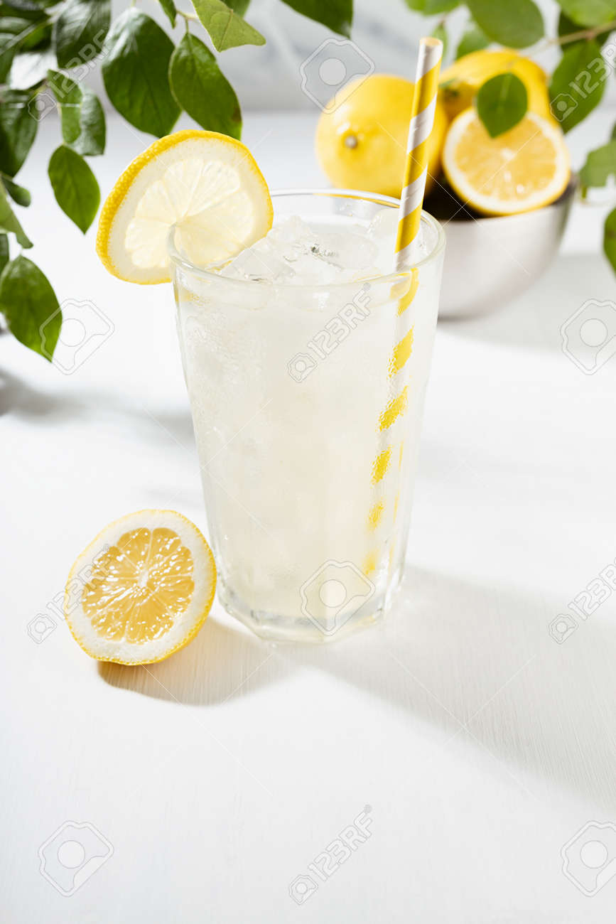 Detox fresh lemon juice of ripe lemons with ice in glass with ingredients in silver bowl, green branch in summer sunlight on white table, marble tile wall, vertical. - 173913858