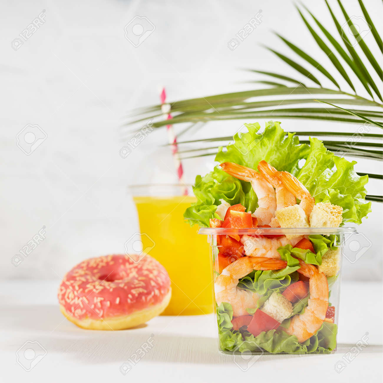 Bright summer lunch set with seafood salad with shrimps, red bell pepper, lettuce, croutons in plastic pack, fresh orange juice, pink donut in white interior with marble tile, palm leaf, square. - 173913716