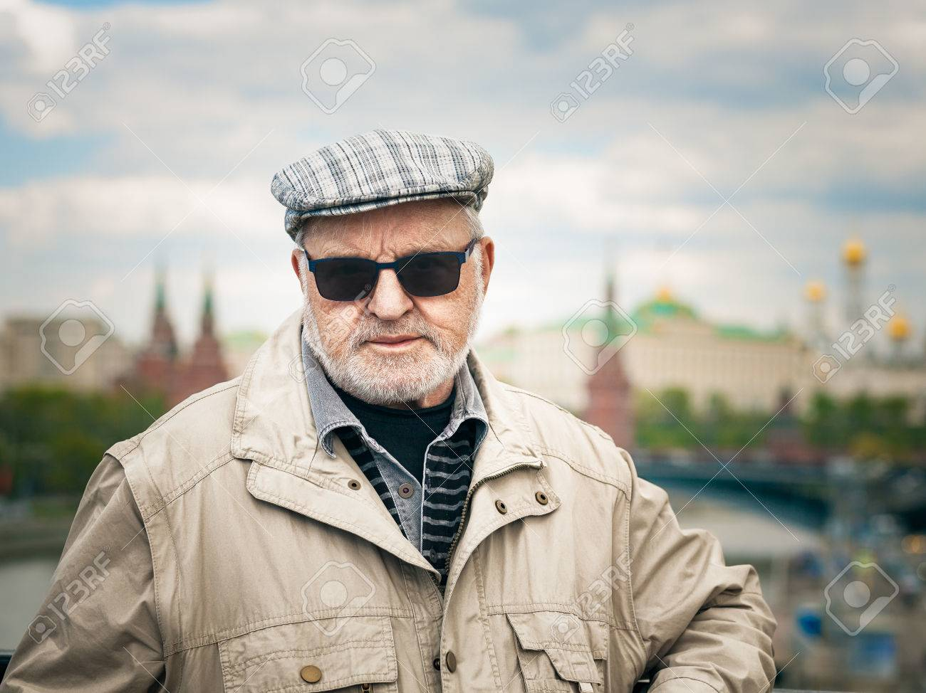417f357fc5f Portrait of old man in sunglasses and cap. Tourist in front of the Kremlin