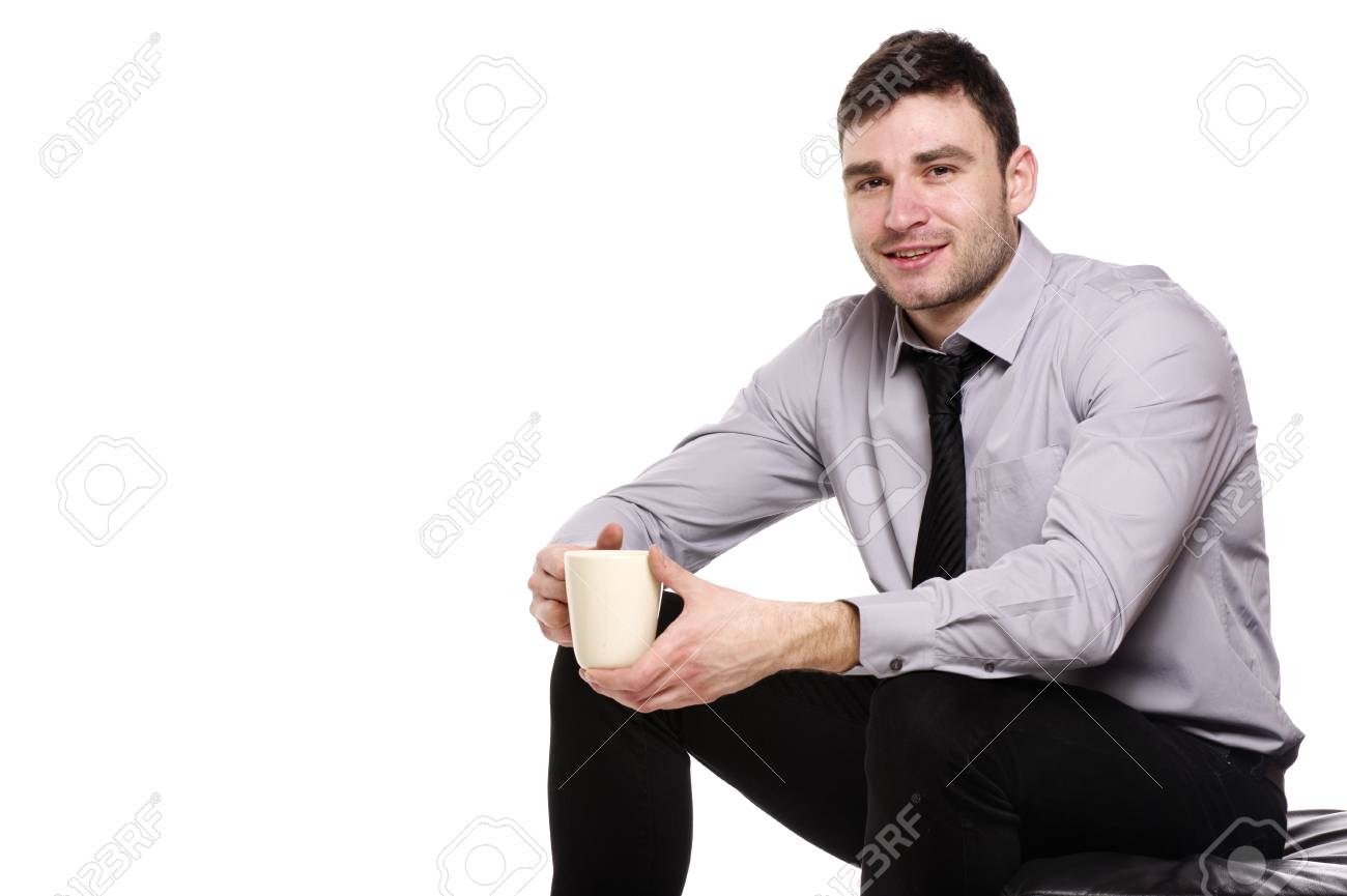 Handsome business man sat isolated on a white background holding a cup of coffee Stock Photo - 18495237