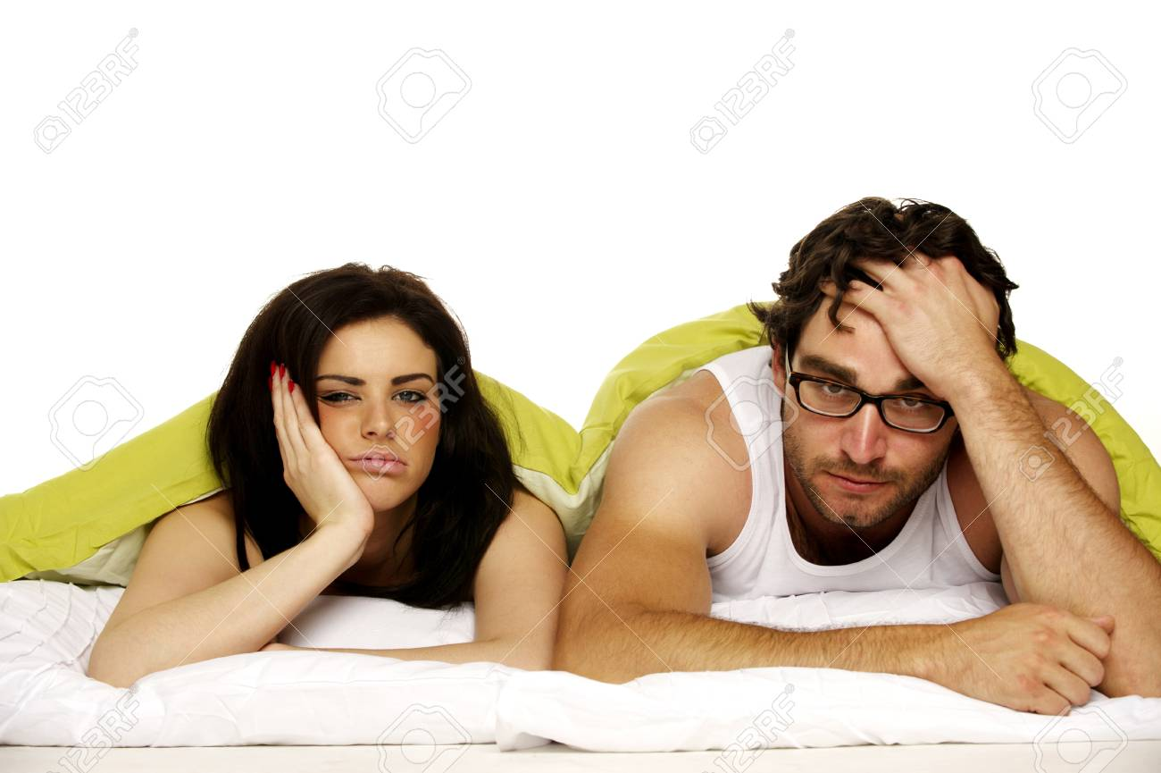 Attractive couple laid in bed under a green duvet looking tired and miserable in the morning Stock Photo - 24373246