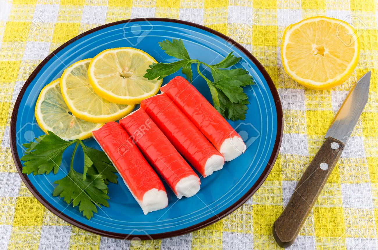Crabe Avec Un Couteau bâtonnets de crabe avec citron et le persil dans la plaque bleue, un