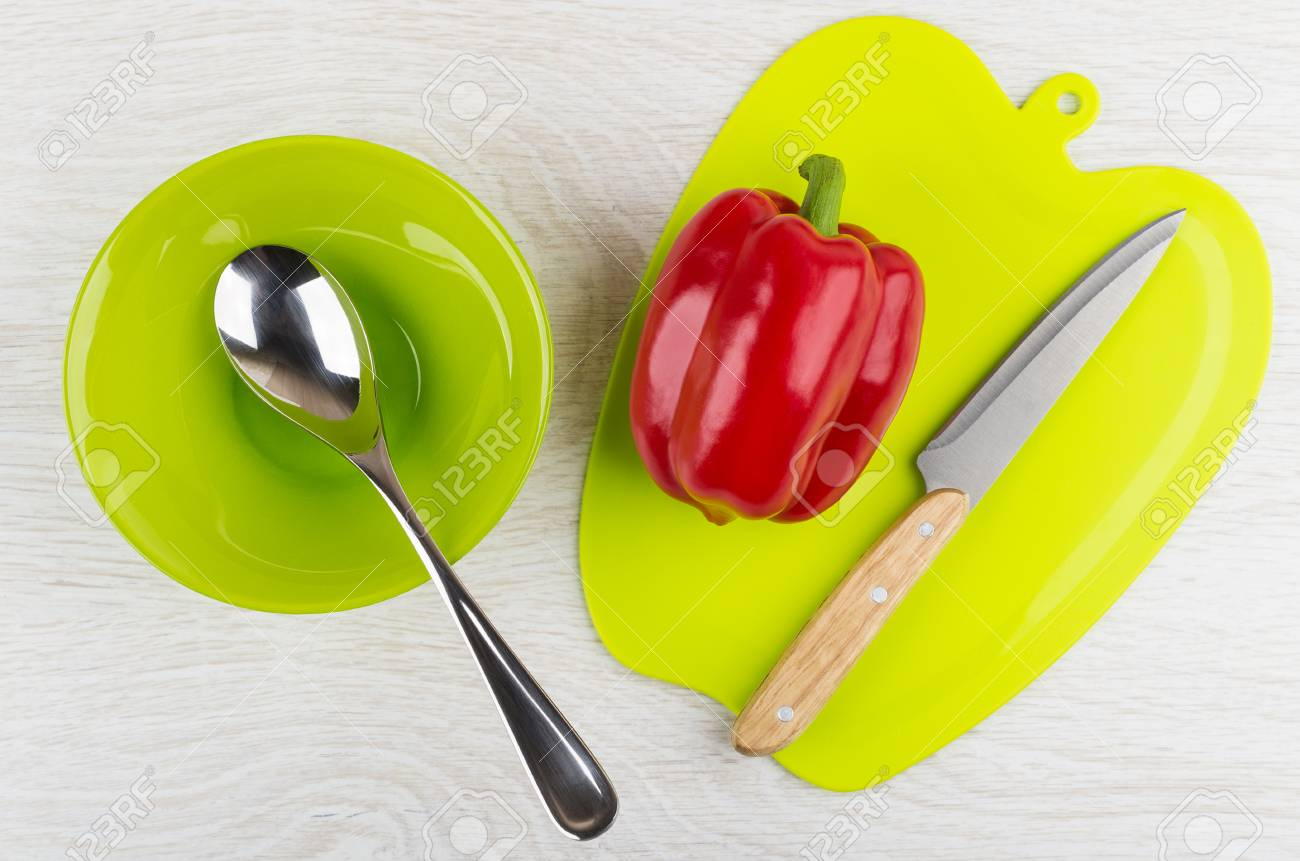Green bowl and spoon, sweet pepper and kitchen knife on plastic..