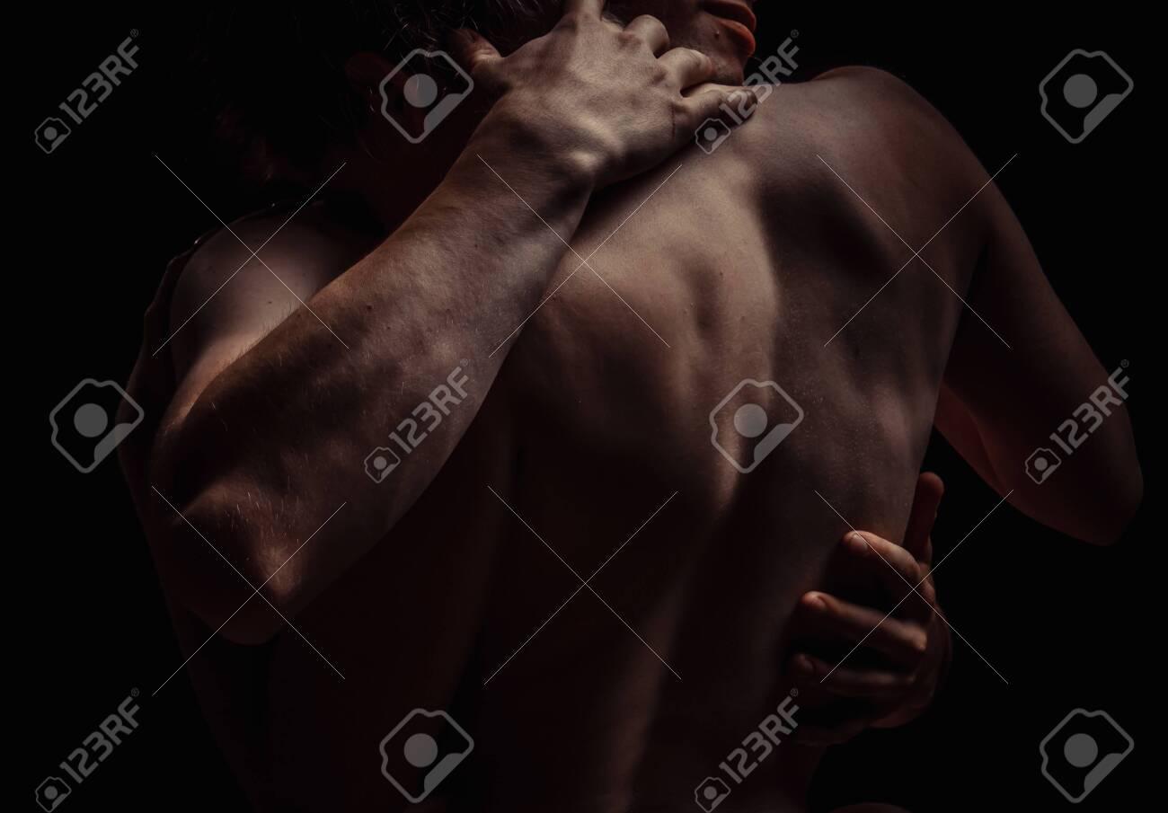 couple on a dark background hugs - 133430987