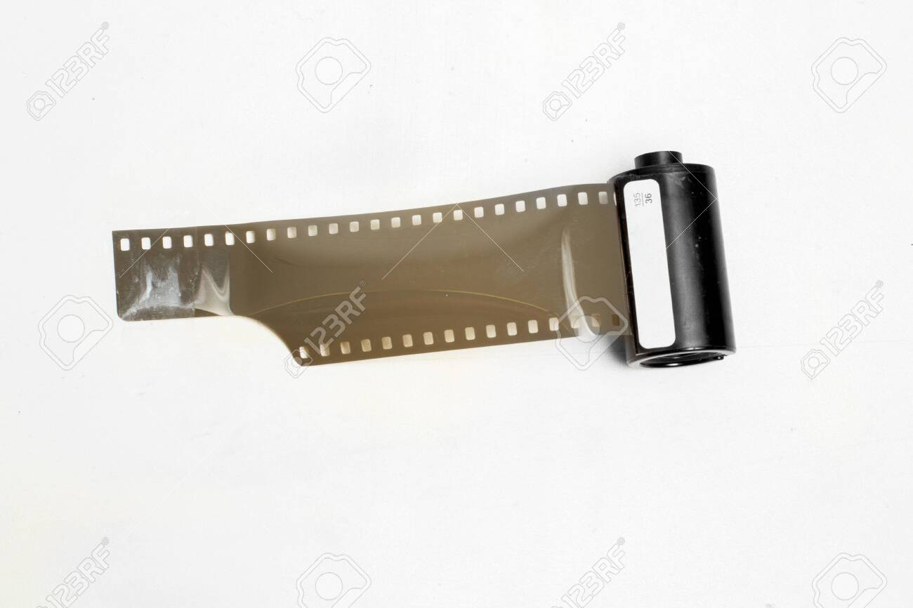vintage photographic film with perforations in the cassette on white background isolate - 147874590