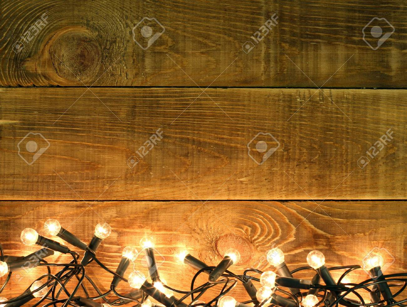 christmas and new year background with decorations glowing garland lights lamp on rustic wooden table board