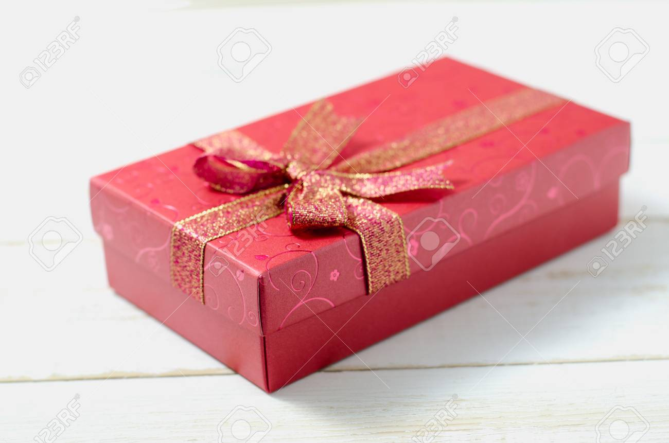 Close Up Of Red Gift Box With Ribbon Bow On White Wooden Table Stock ...