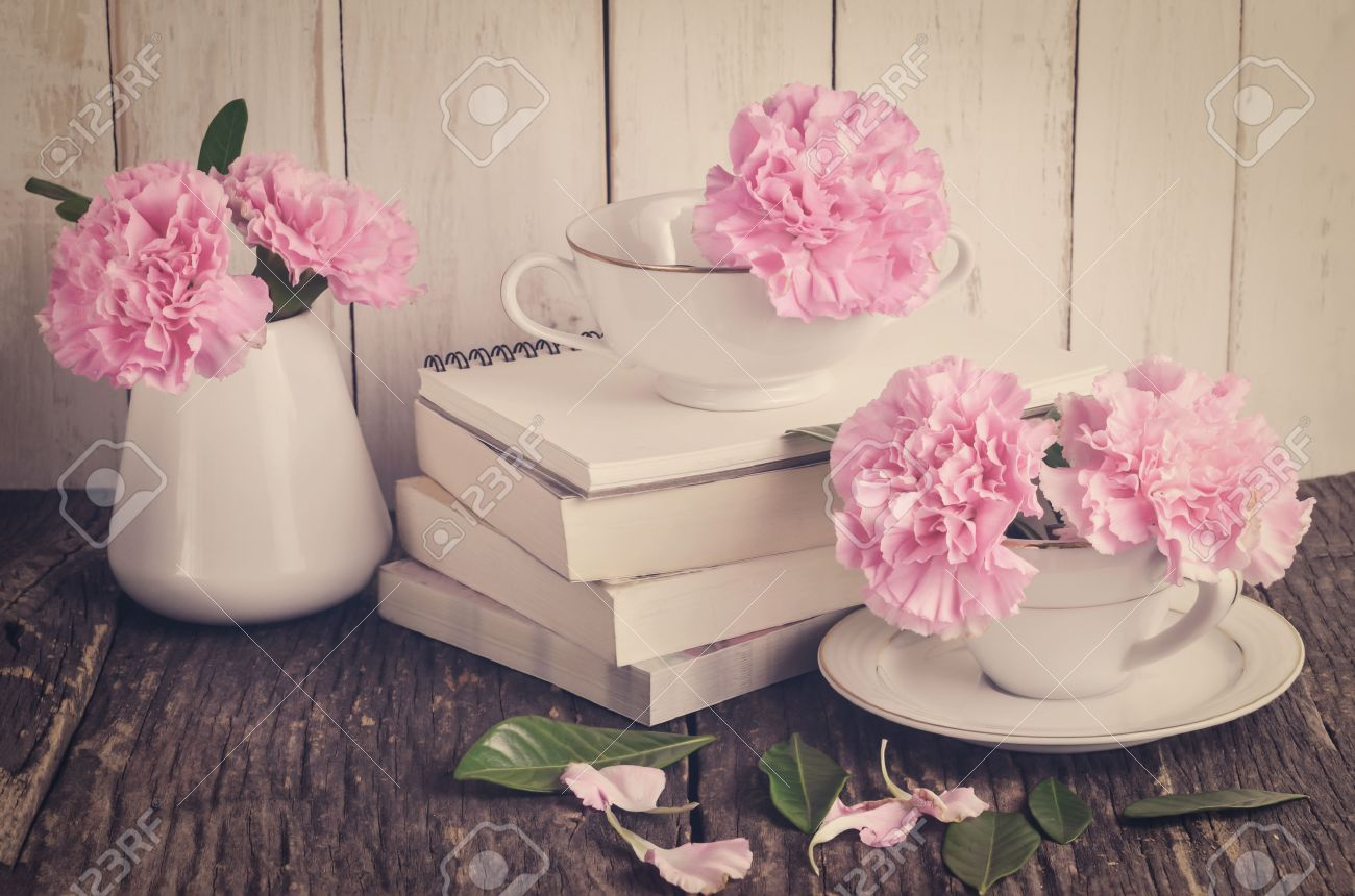 Pink pastel carnation flowers in white tea cup and vase on pile pink pastel carnation flowers in white tea cup and vase on pile of books on wooden mightylinksfo