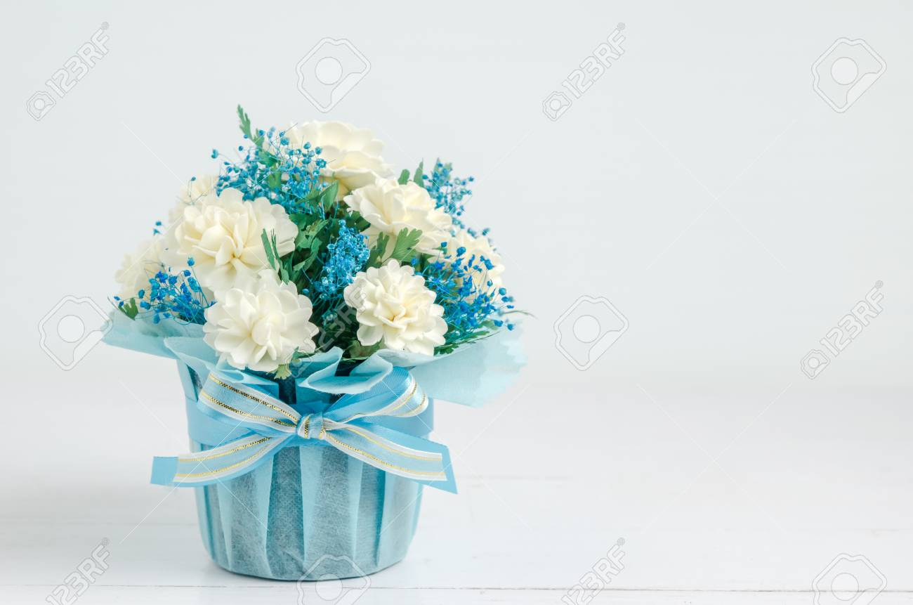 Close up of beautiful jasmine flower bouquet with blue ribbon close up of beautiful jasmine flower bouquet with blue ribbon bow on white wooden background izmirmasajfo Image collections