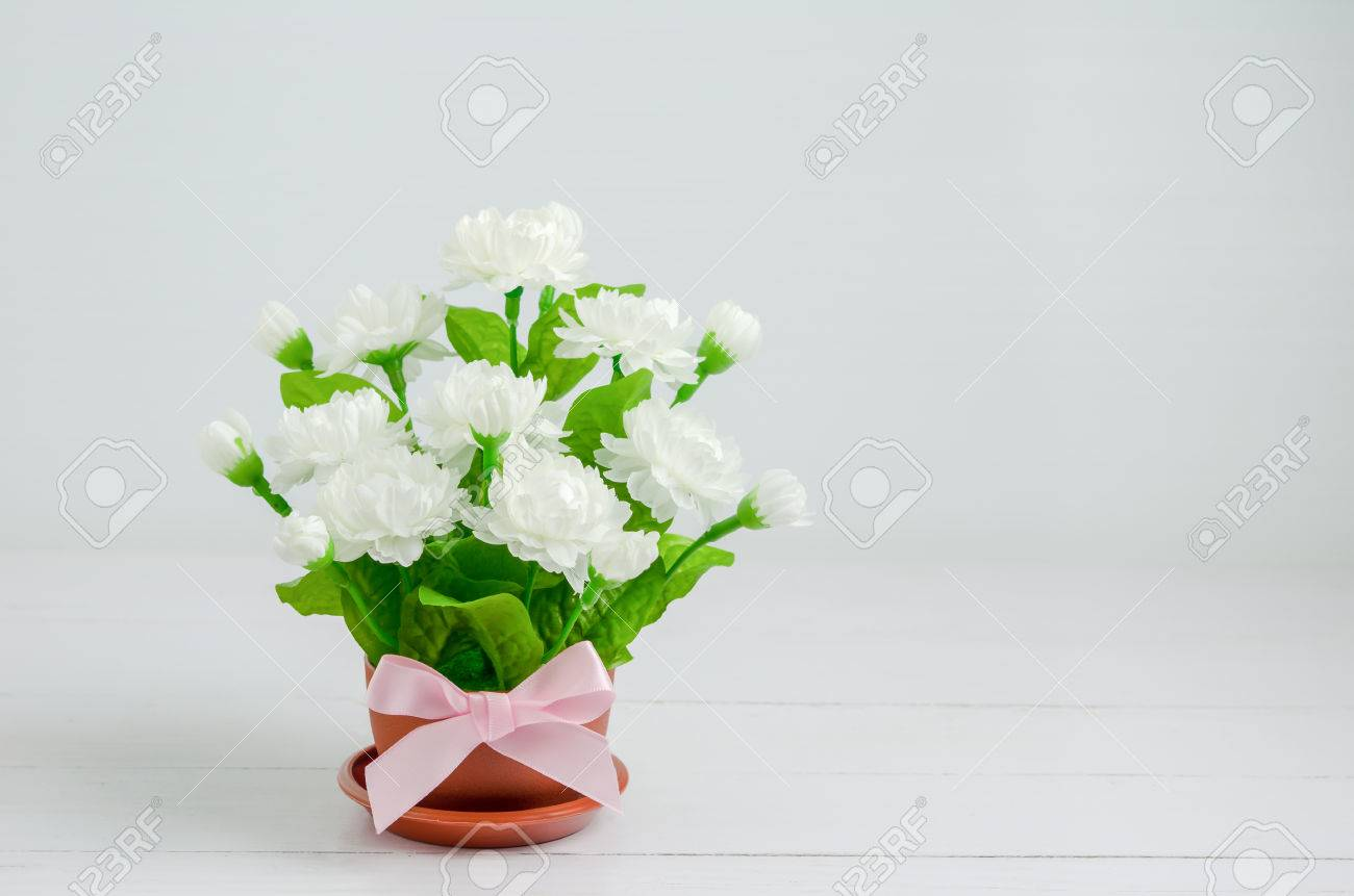Close up of artificial jasmine flower bouquet with pink ribbon close up of artificial jasmine flower bouquet with pink ribbon bow at small flower pot on izmirmasajfo Image collections