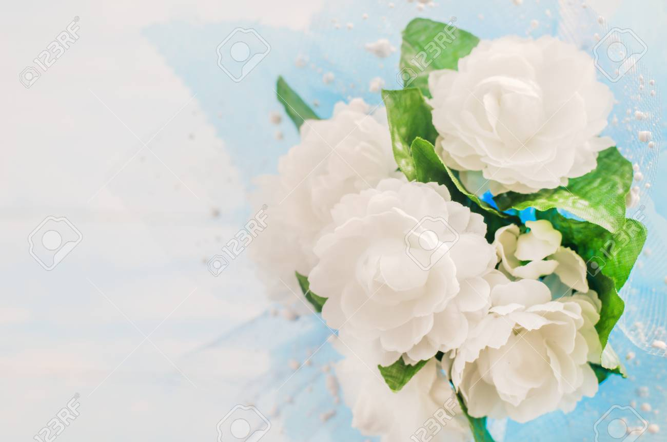 Close up of artificial jasmine flower bouquet with blue ribbon close up of artificial jasmine flower bouquet with blue ribbon bow on white and blue wooden izmirmasajfo Image collections