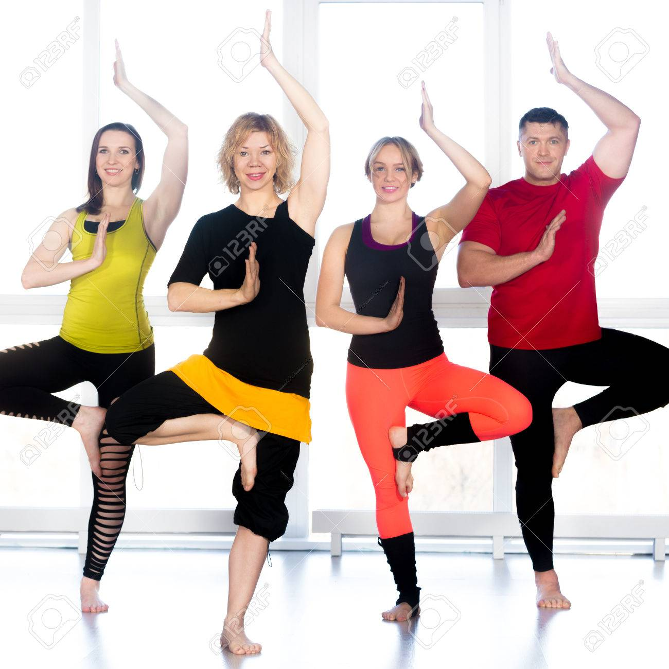 Group of four happy people doing yoga training in class, standing..