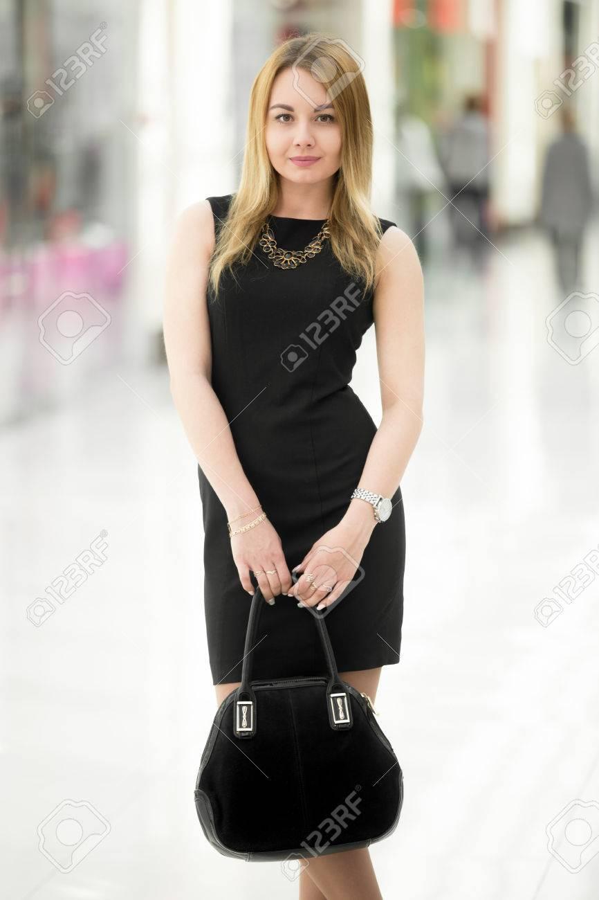 Sonriente mujer joven que llevaba el bolso corto vestido negro celebración de gamuza en el moderno edificio