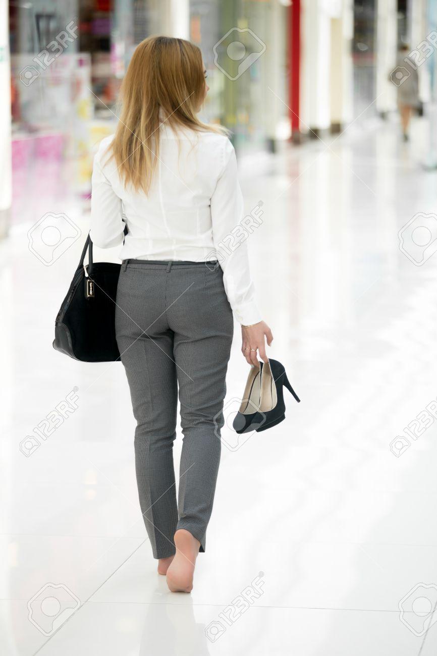 0df66858c494 Foto de archivo - Mujer joven en ropa de estilo de oficina que llevan en la  mano los zapatos de tacón alto, caminando descalzo en edificio  contemporáneo, ...