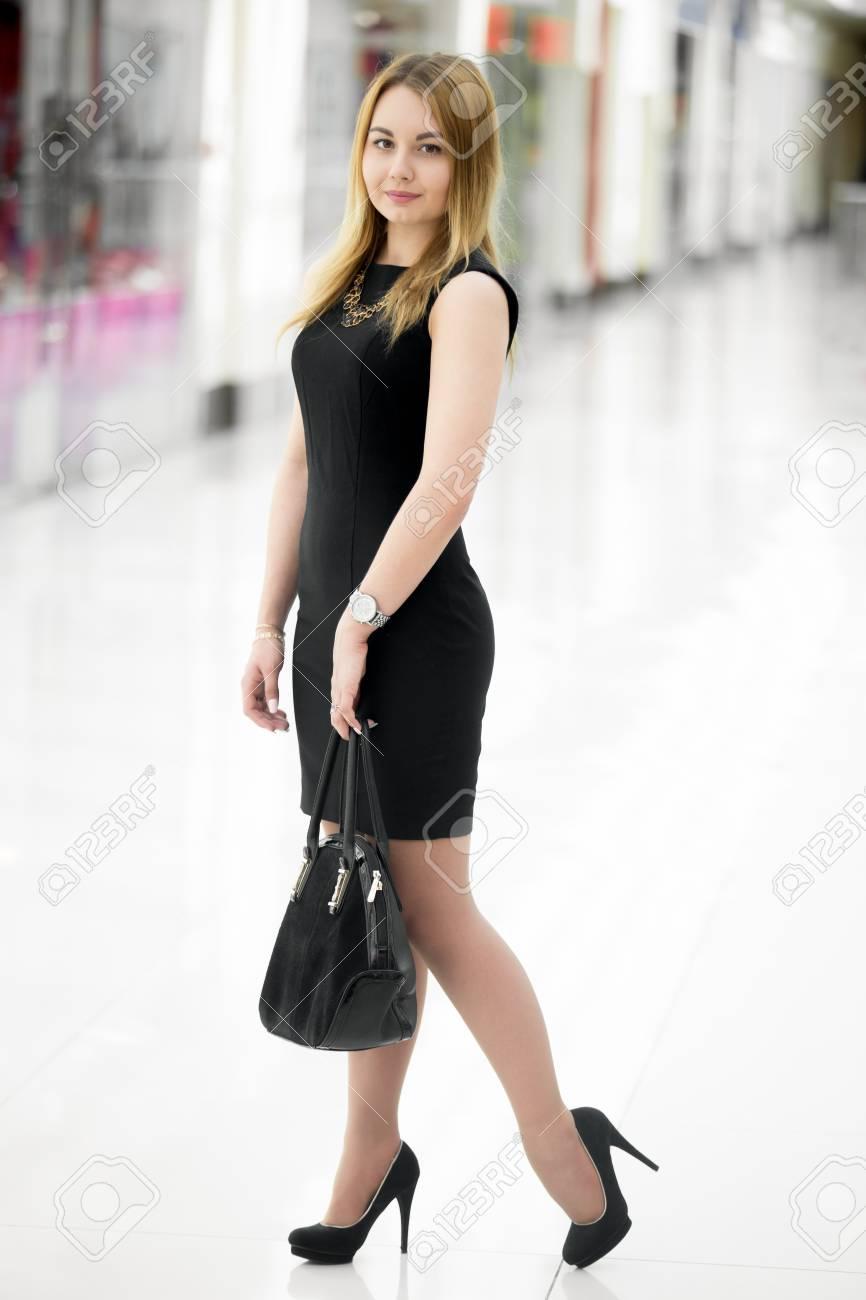 Mujer joven hermosa con un vestido corto negro lindo y zapatos de tacón alto que sostienen el bolso de gamuza en el centro comercial