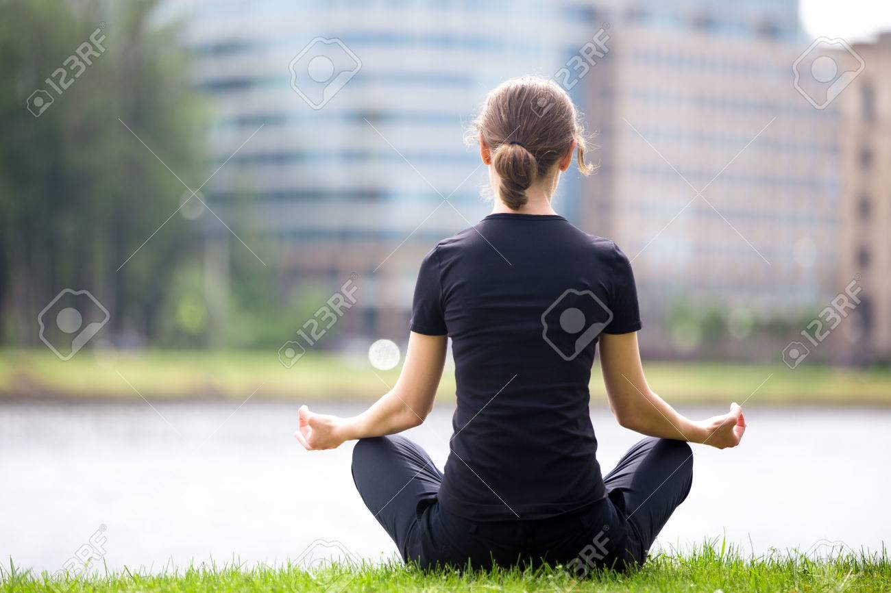 stock photo young woman sitting cross legged on river bank in front of blue glass modern office building meditating practicing yoga easy pose blue glass top modern office