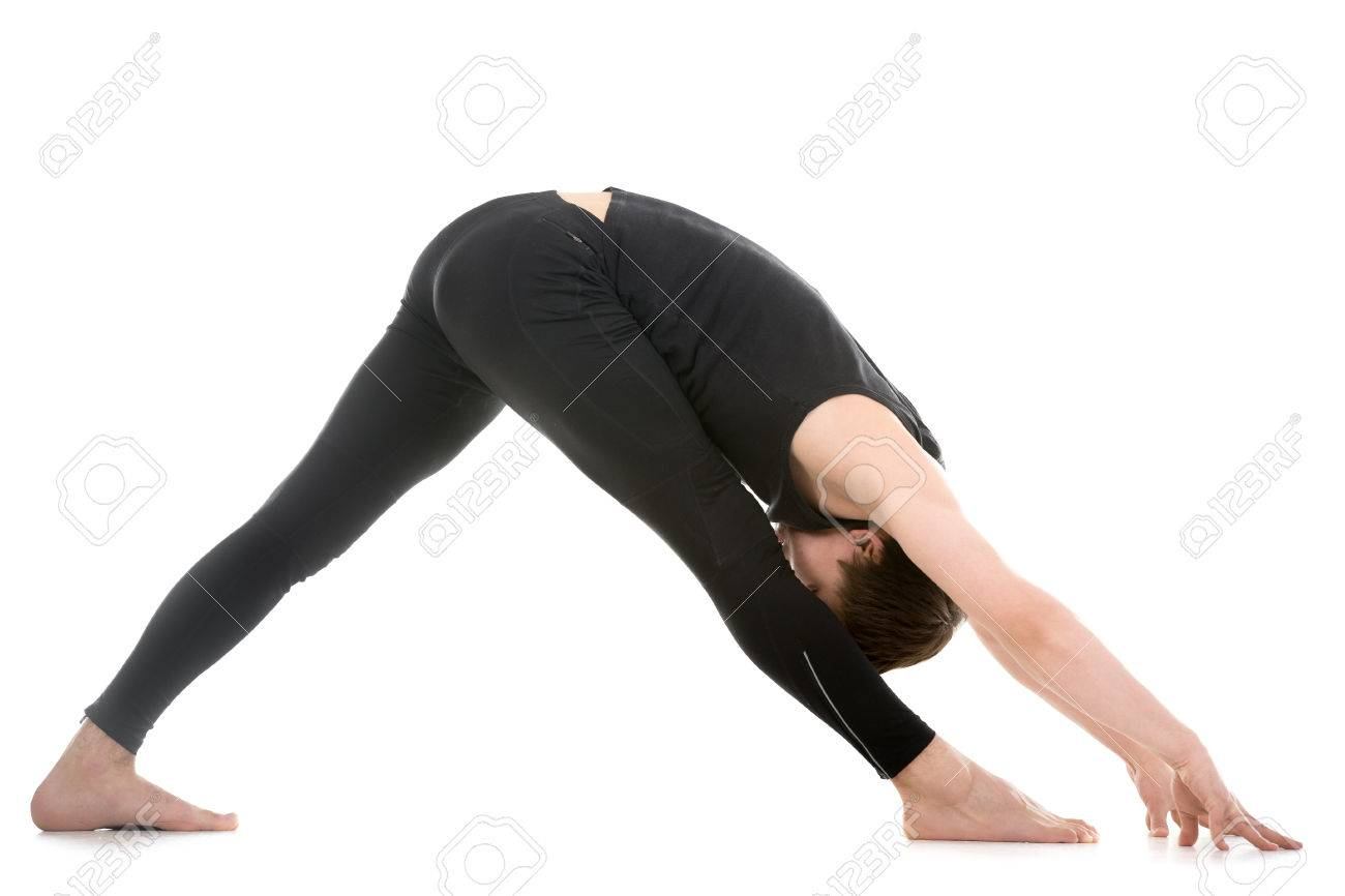 Profile of sporty young man working out, standing in yoga Pyramid