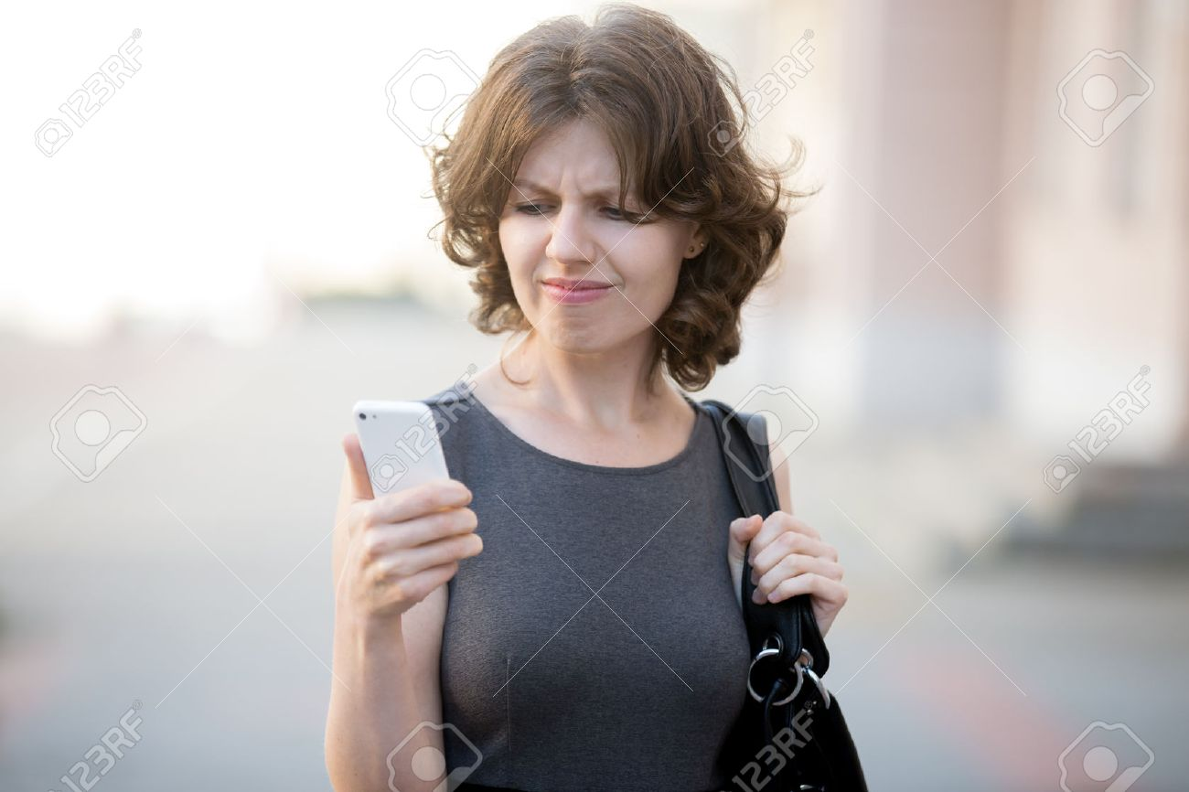 Frustrated office worker on the phone holding stock photo image - Frustrated Portrait Of Stressed Office Young Woman Holding Cellphone In Hands On The City Street