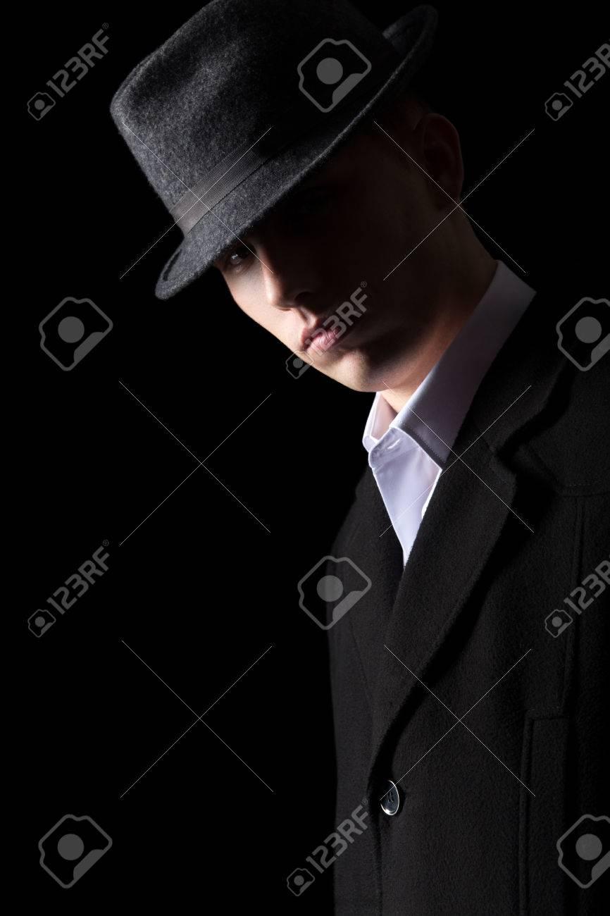 homme le noirun dans studio clé fond faible Bel chapeau sur éclairage dans en brutal l'obscuritétourné manteau et le regardant Fc3KJTl1