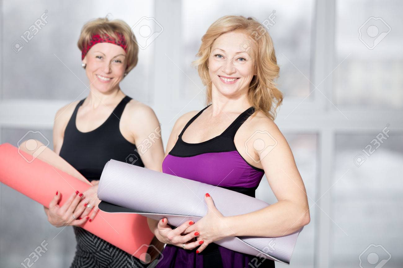 Indoor portrait of group of two cheerful attractive fit senior women posing holding fitness mats, working out in sports club class, happy smiling, looking at camera with friendly expression - 50746738