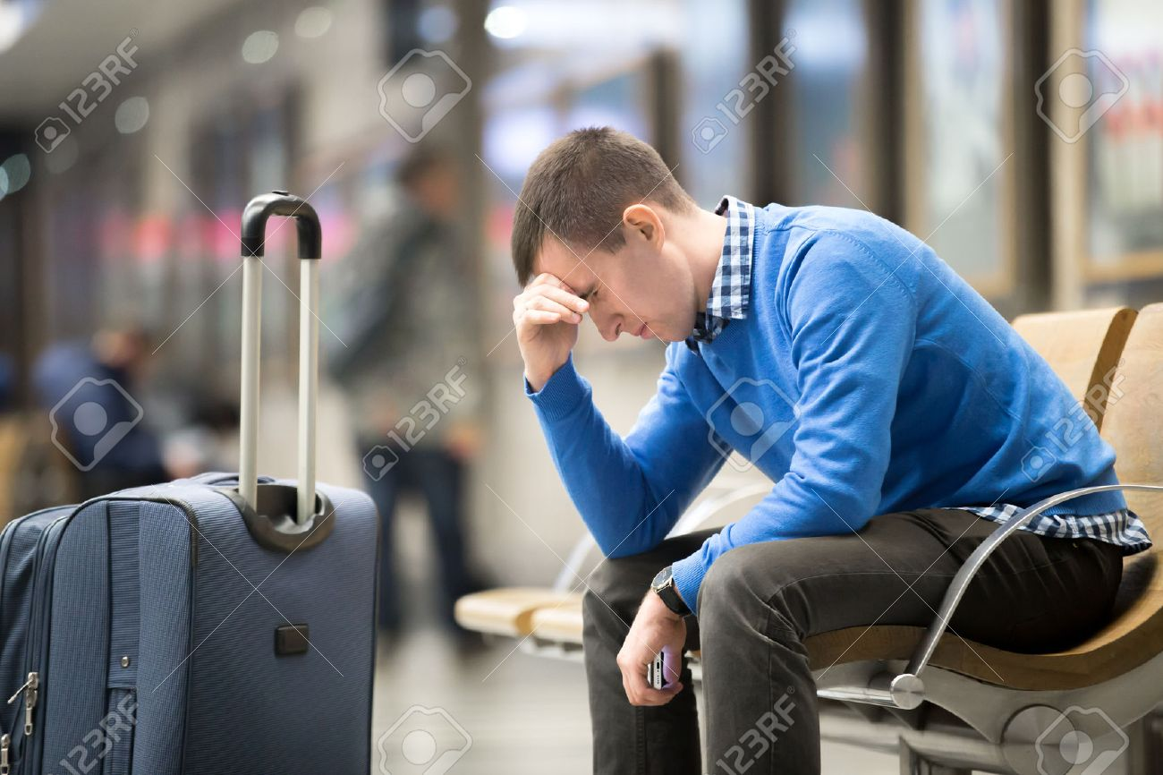 Portrait of young handsome guy wearing casual style clothes waiting for transport. Tired traveler man travelling with suitcase sitting with frustrated facial expression on a chair in modern station - 54552648