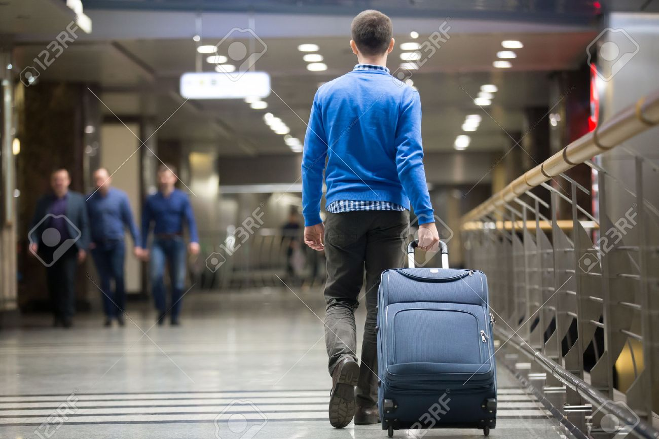 Young man pulling suitcase in modern airport terminal. Travelling guy wearing smart casual style clothes walking away with his luggage while waiting for transport. Rear view. Copy space - 54552652