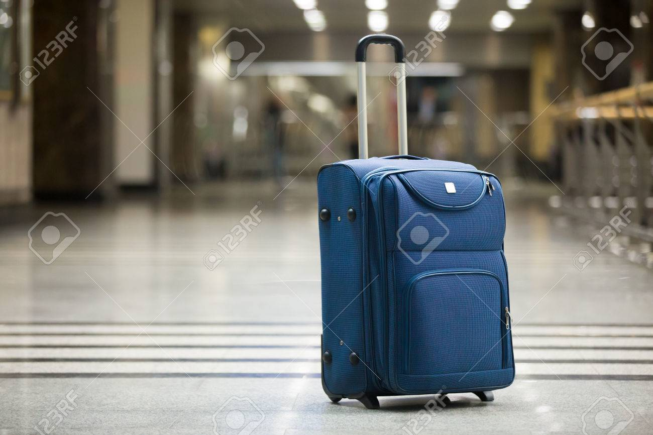 Large blue wheeled suitcase standing on the floor in modern airport terminal. Copy space - 54552677