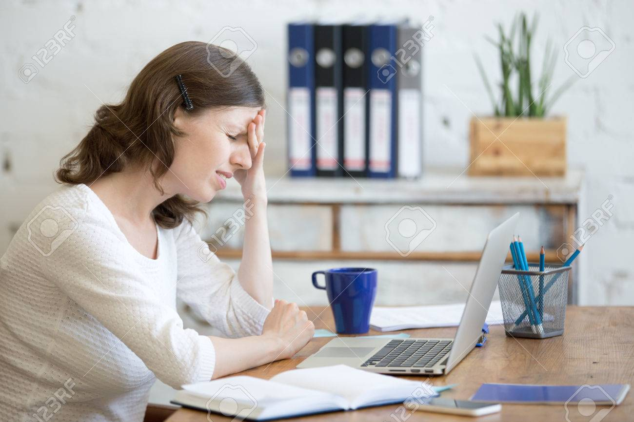 Young stressed businesswoman sitting in front of laptop and touching head with pained expression. Business person feeling pain, suffering from migraine after working on pc, overworked or depressed - 62316083