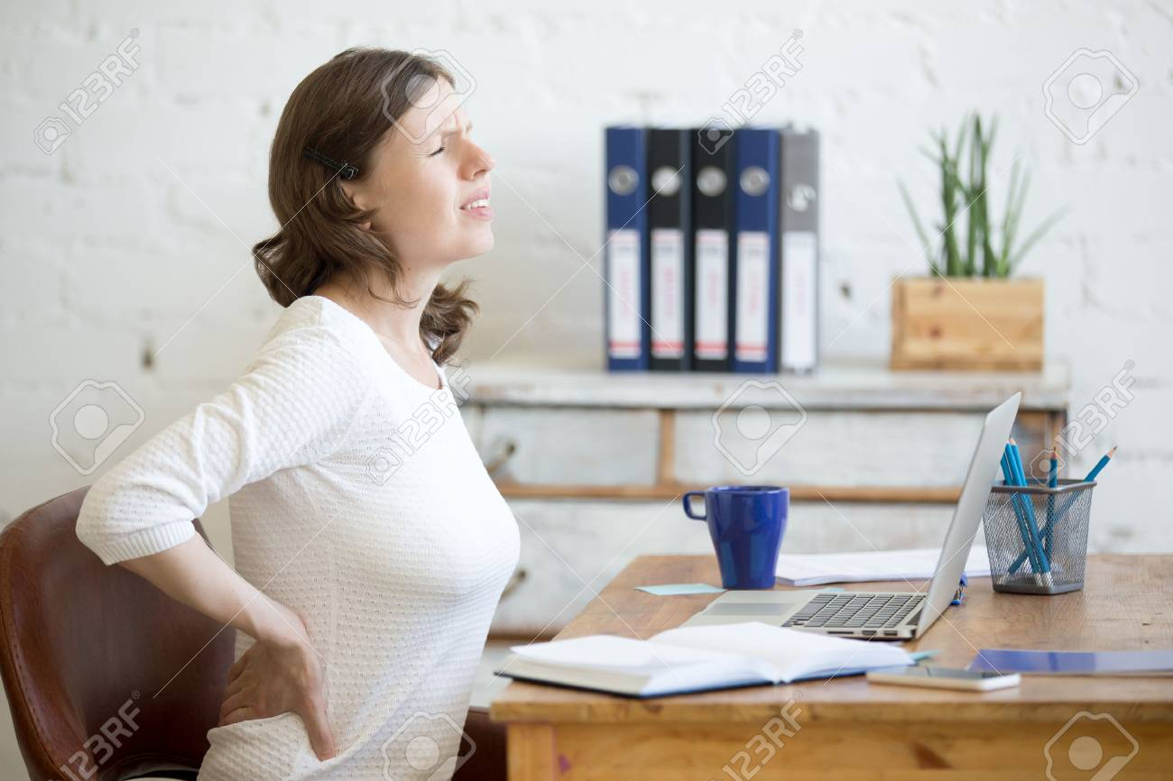 Young stressed businesswoman sitting in front of laptop and holding her waist with pained expression. Business woman feeling pain, touching aching back, suffering from backache after working on pc - 62328995