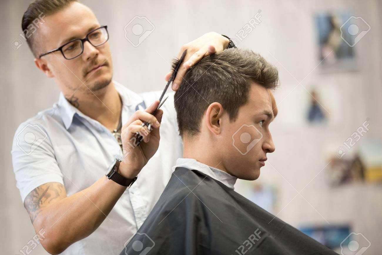 Plan intérieur du processus de travail dans le salon de coiffure moderne.  Vue latérale portrait de jolie jeune homme se coupe de cheveux à la mode.  ...
