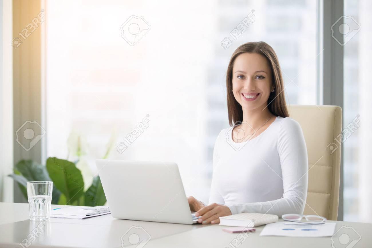Young Smiling Female Receptionist At The Modern Office Desk With A ...