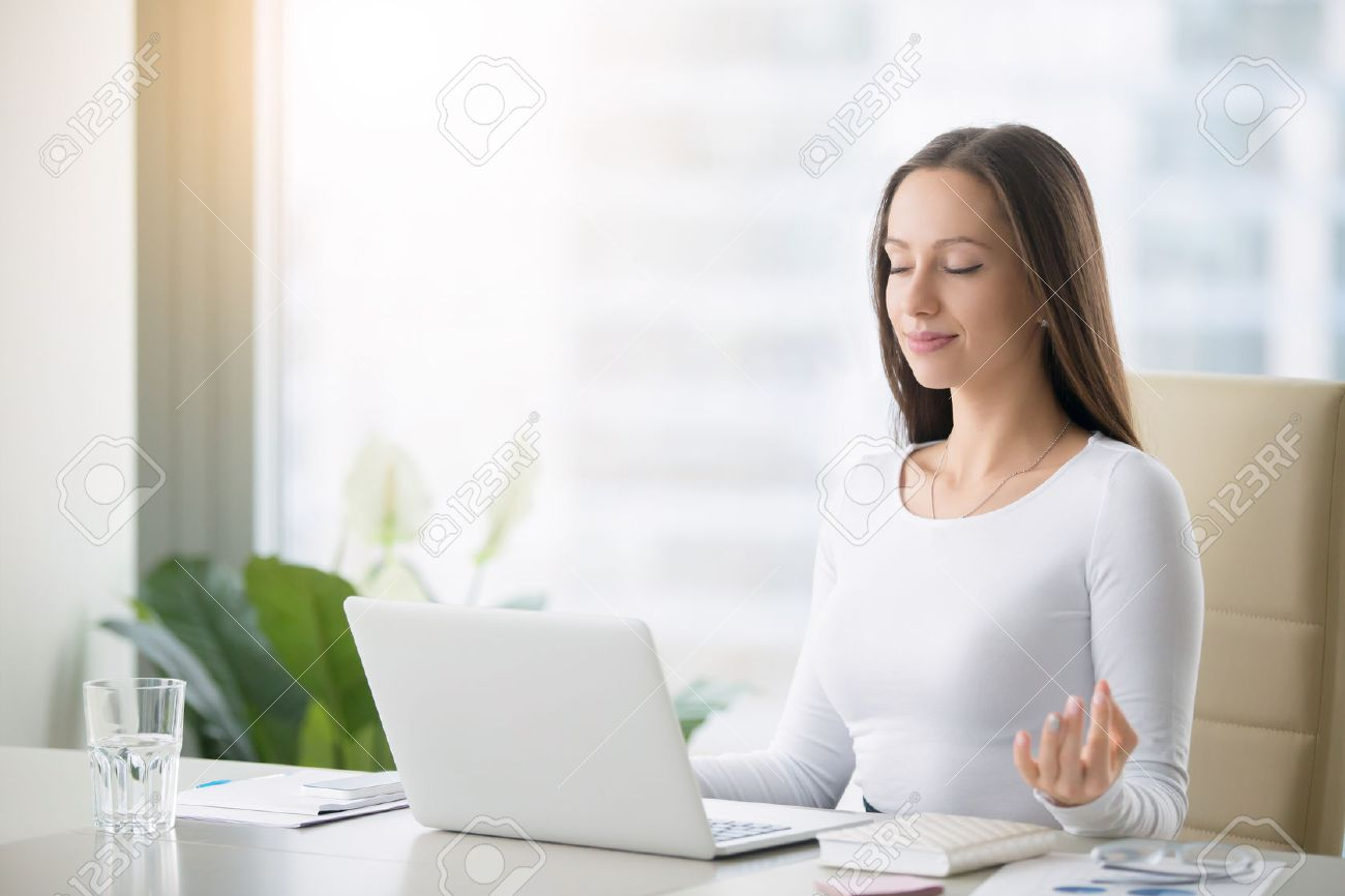 meditation in office. Stock Photo - Young Woman Near The Laptop, Practicing Meditation At Office Desk, In Front Of Online Yoga Classes, Taking A Break Time For O