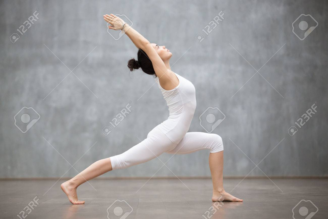 Side view portrait of beautiful young woman wearing white tank top working out against grey wall, doing yoga or pilates exercise. Standing in Warrior one pose, Virabhadrasana. Full length - 68448429