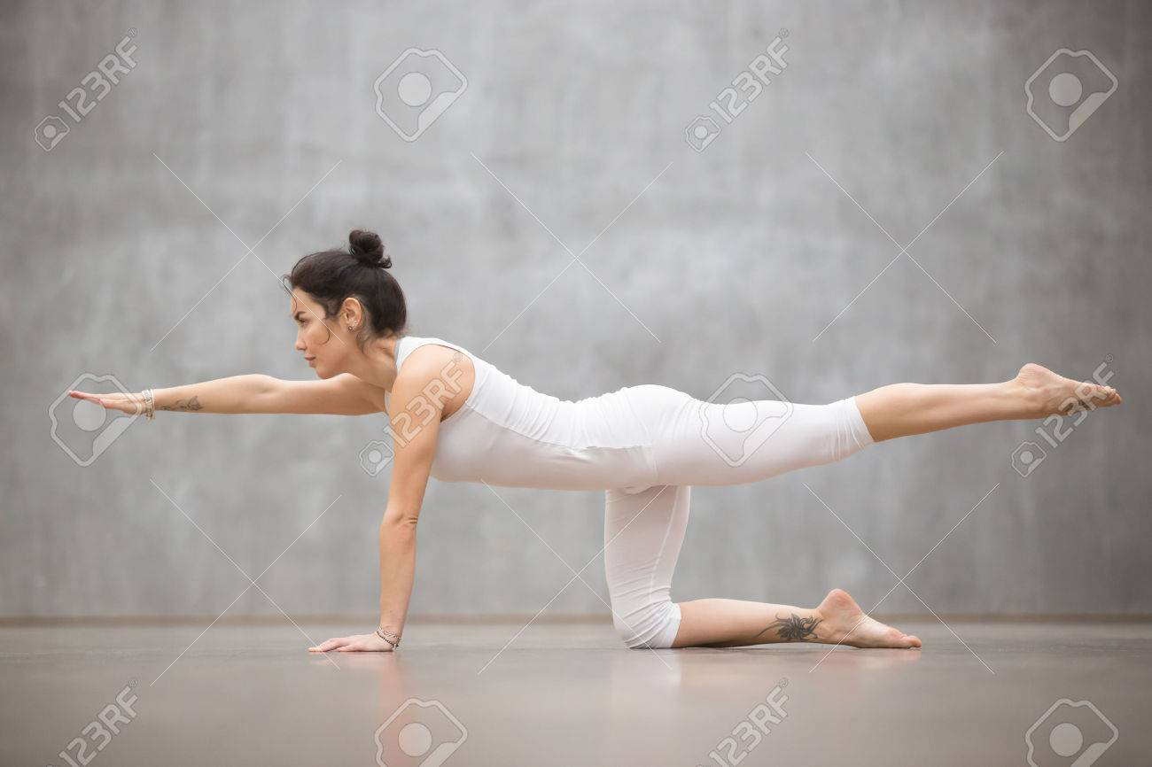 Side view portrait of attractive young woman with beautiful tattoo working out against grey wall, doing yoga, pilates balancing exercise. Bird dog, chakravakasana pose. Full length - 68452316