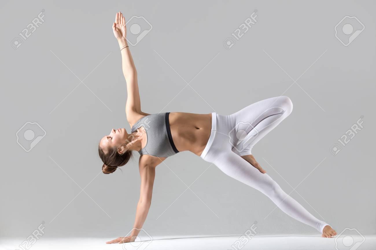 Jeune Femme Seduisante Pratiquer Le Yoga Etirement Dans L Exercice De Planche Laterale Vasisthasana Pose Travailler Avec Des Vetements De Sport Un Pantalon Blanc Une Pleine Longueur A L Interieur Isole Sur Fond De