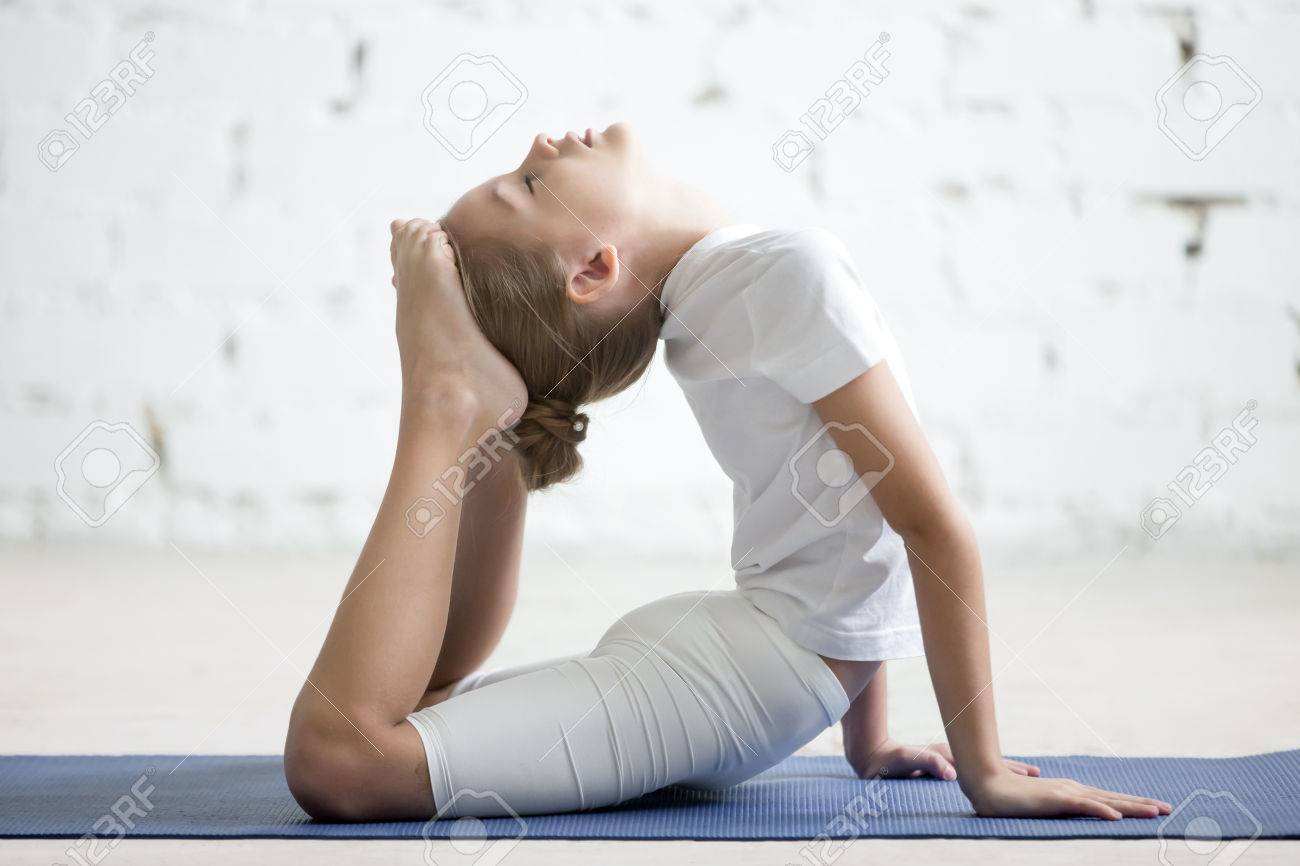 Girl Child Practicing Yoga On Blue Mat Stretching In Raja Bhudjangasana Exercise King Cobra