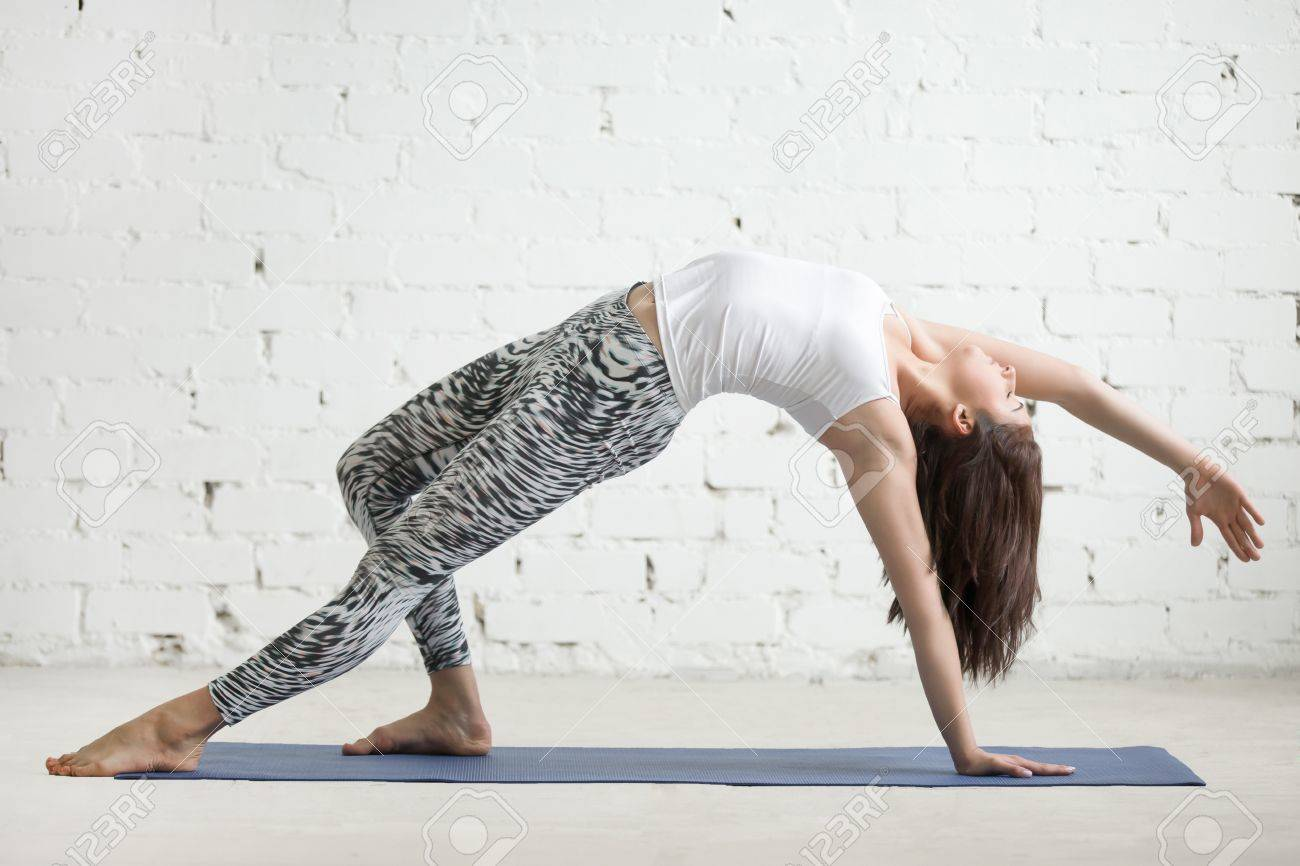 Young attractive woman practicing yoga, doing Wild Thing, Flip-the-Dog..