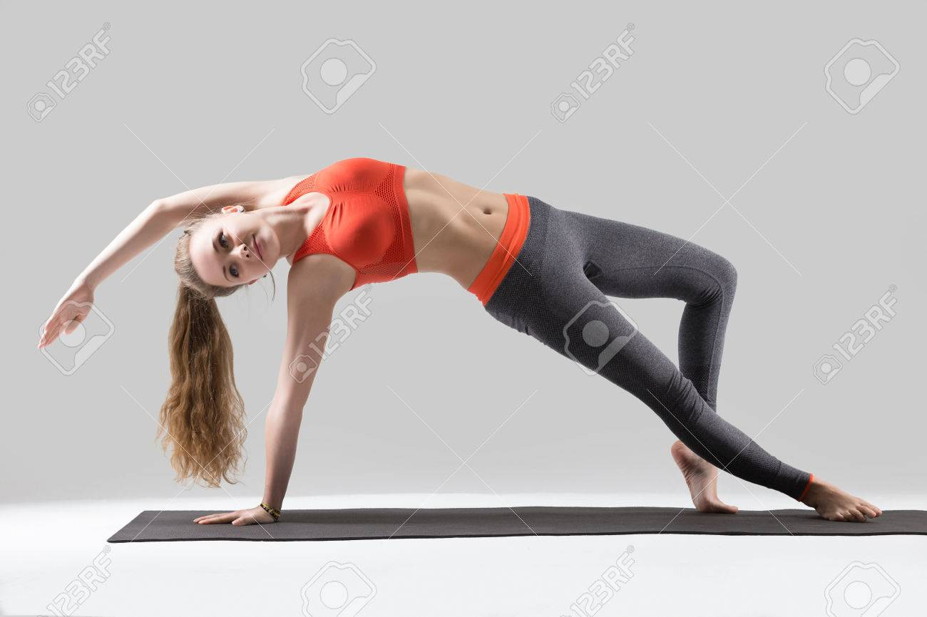 Young yogi attractive woman practicing yoga, doing Wild Thing,..