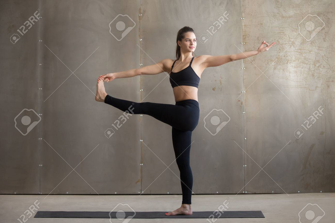 Young woman practicing yoga, standing in Parivrtta Utthita Hasta..