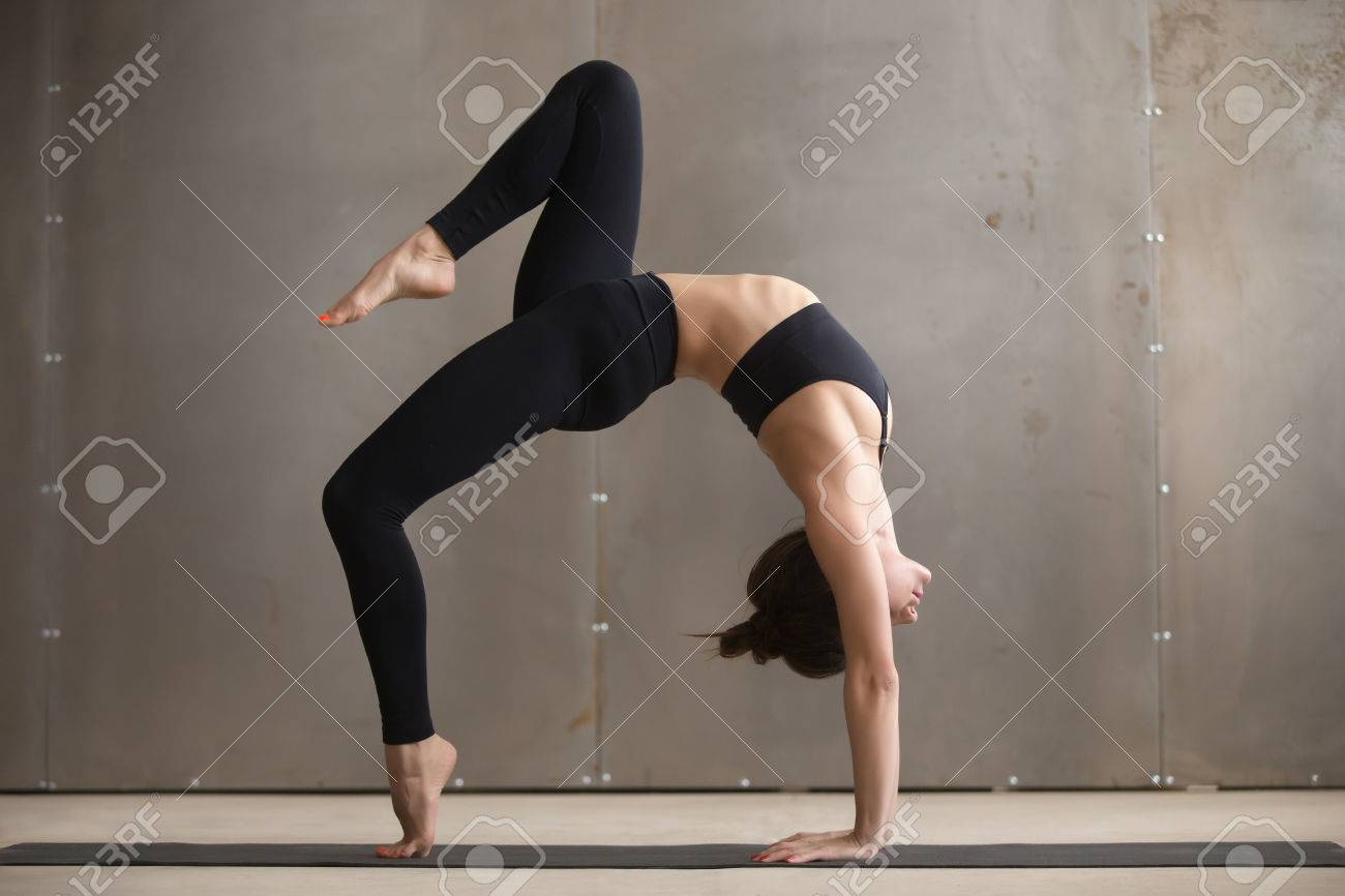 def301037ad29 Stock Photo - Young attractive yogi woman practicing yoga, standing in  Bridge exercise, One legged Wheel pose, working out, wearing black  sportswear, ...