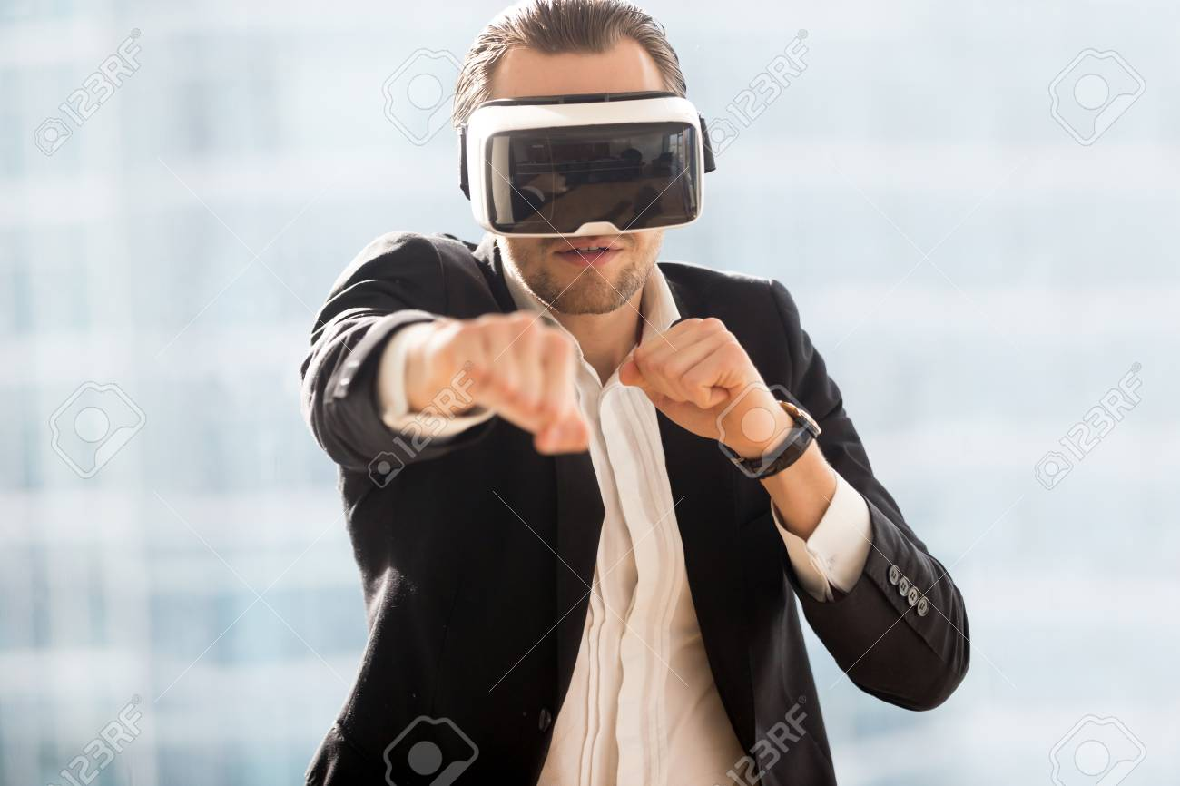 164765df6eef Man in business suit boxing with virtual reality glasses on head. Guy  playing computer fighting