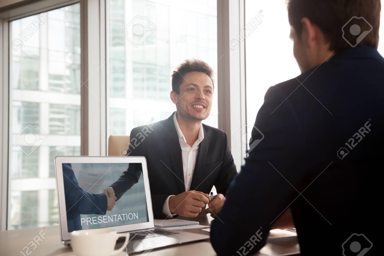 smiling investment broker showing digital presentation on laptop