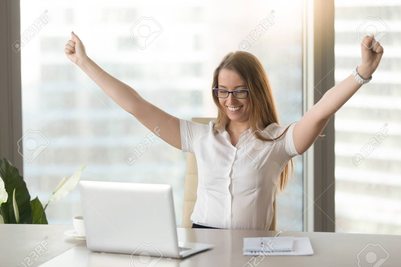 Excited smiling businesswoman celebrating business success at workplace, raising hands looking at laptop screen, feeling happy about great win, good news online, positive result, passed exam, got job - 86667378
