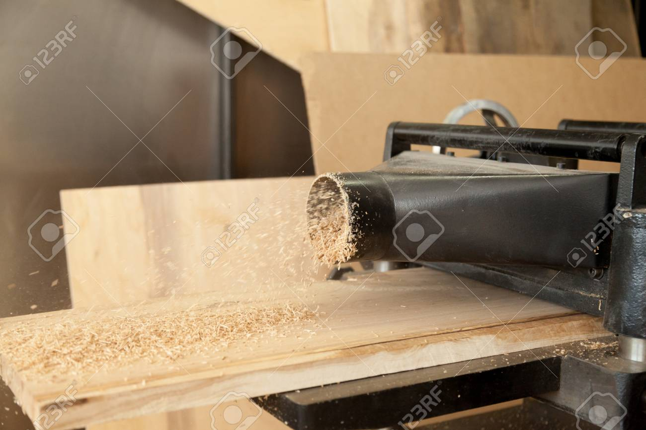 Close up image of thickness planer machine cutting board of hard