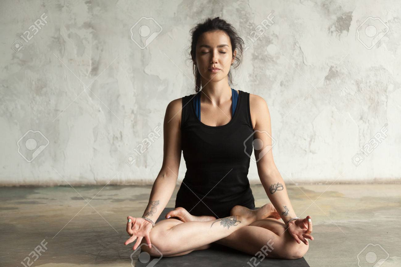 Young Woman With Tattoo Practicing Yoga Sitting In Padmasana Stock Photo Picture And Royalty Free Image Image 87547297