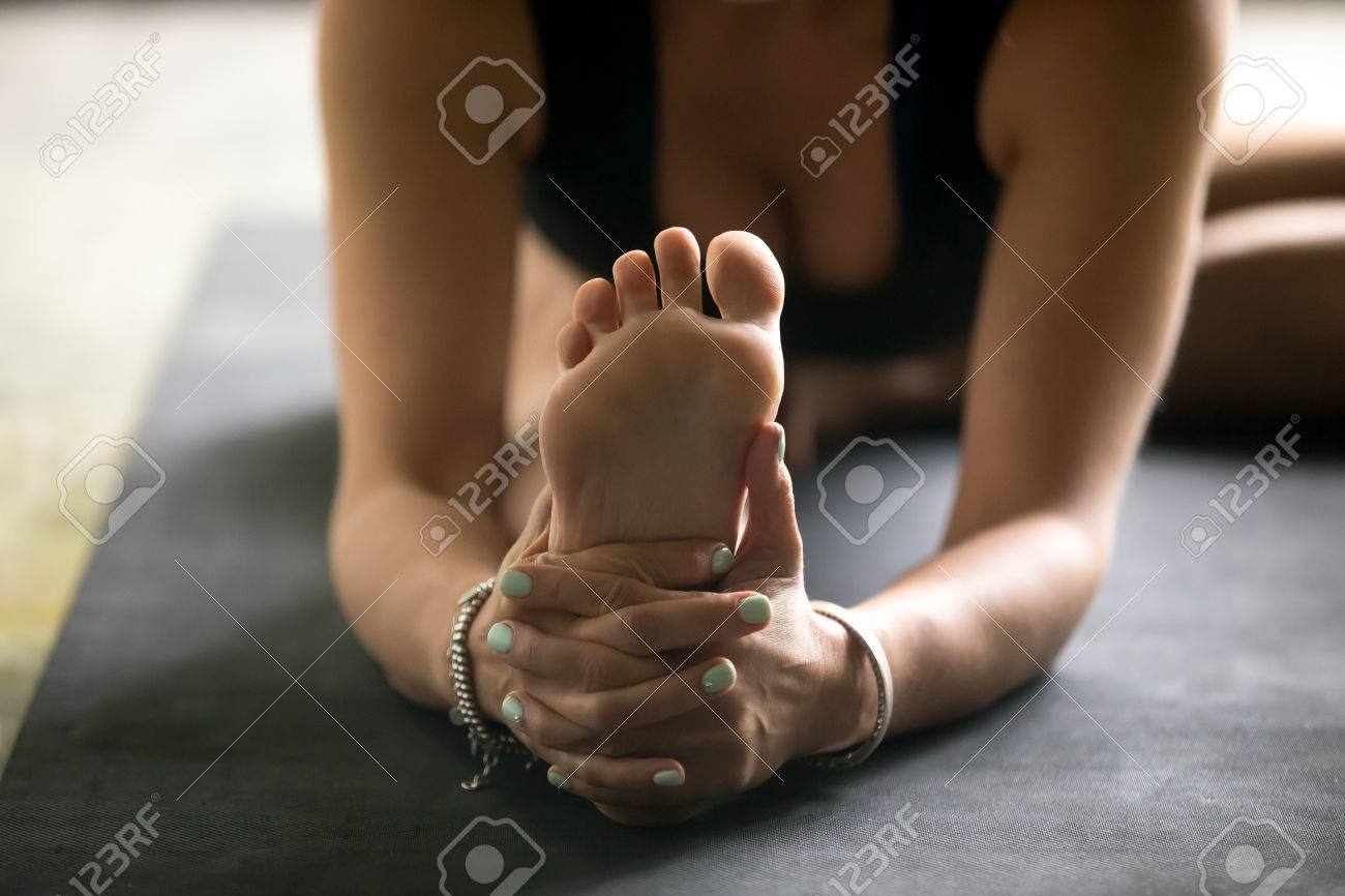 Close up sole image, woman practicing yoga at home, sitting in Janu Sirsasana exercise, Head to Knee Forward Bend pose, working out, wearing sportswear, black top, mat background. Wellness concept - 87342646